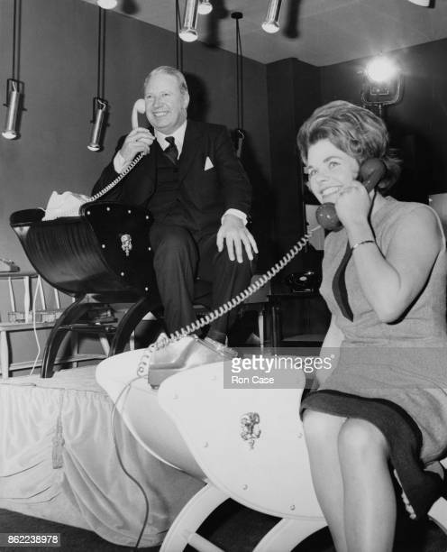 Edward Heath the Trade Secretary and President of the Board of Trade talks to television presenter Judith Chalmers on the telephone after opening the...