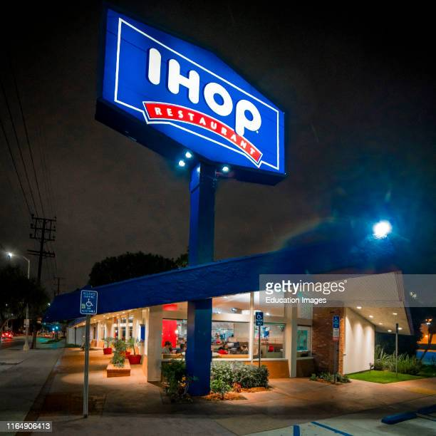 Edward Hopper style view of Los Angeles California IHOP at night with neon sign on