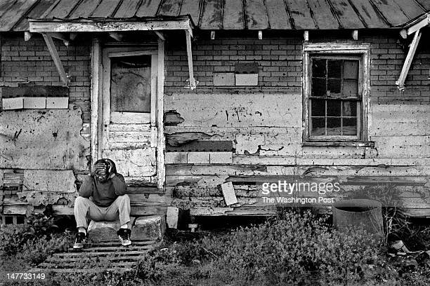 FILE Edward Johnson is exhausted after getting home from work in Bayview Virginia on May 9 1998 He rests outside of his $45 per month rental unit