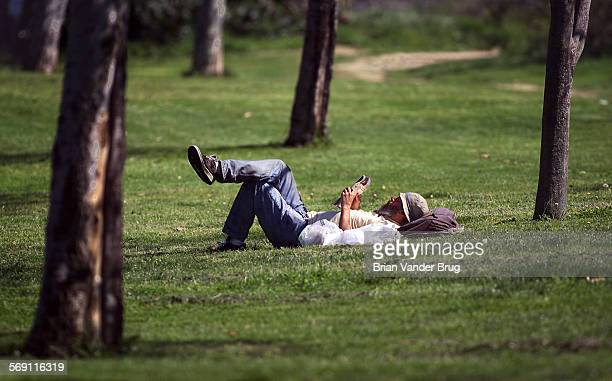 Edward King of Reseda found a sunny spot to read and relax among the trees at the Sepulveda Dam Recreation Area Tuesday March 13 2001 The temperature...