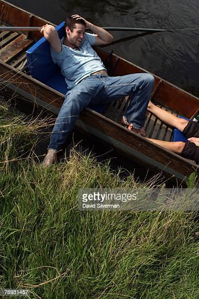 Edward Quigley and Katie Southwell both residents of this university city relax in a punt alongside the bank of the Cherwell river as sunny weather...