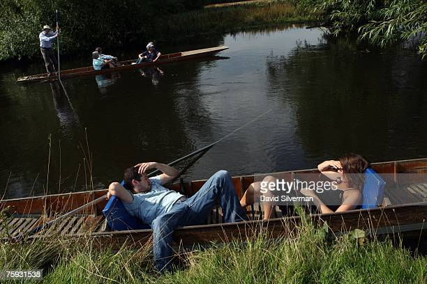 Edward Quigley and Katie Southwell both residents of this university city relax in a punt alongside the bank of the Cherwell river while another boat...