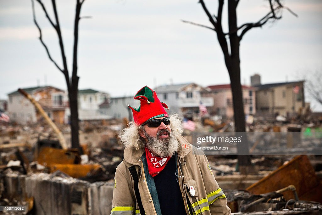 Edward 'Roaddawg' Manley, a volunteer and honorary firefighter with the Point Breeze Volunteer Fire Department, steps back after decorating a Christmas Tree December 25, 2012 in the Breezy Point neighborhood of the Queens borough of New York City. Residents are still struggling to recover from a massive fire that destroyed over 100 homes during Superstorm Sandy.