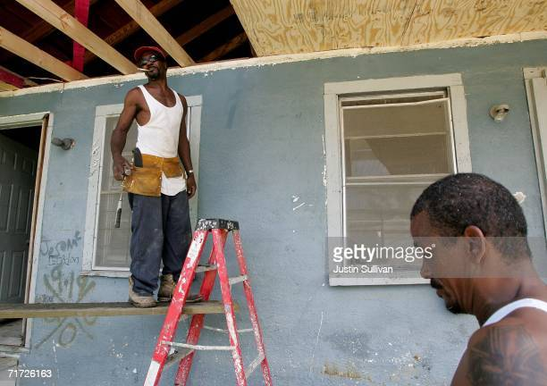 Edward Robinson and his friend Pernell Wade work on Robinson's storm damaged home August 27 2006 in the Lower Ninth Ward of New Orleans Louisiana...
