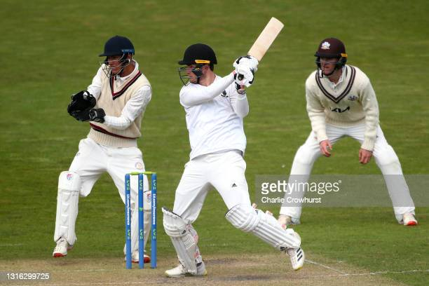 Edward Taylor of Sussex hits out while Surrey wicket keeper Billy Mead looks on during the Second Eleven Championship match between Sussex 2nd XI and...