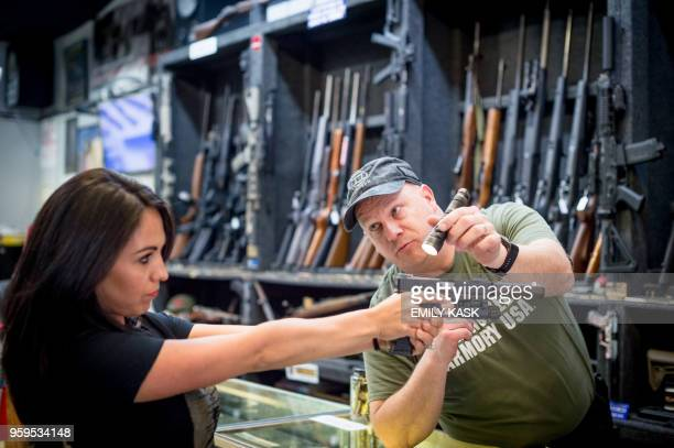 Edward Wilks, owner of Tradesmen Gun Store and Pawnshop helps Lauren Boebert with a firearm at his store in Rifle, Colorado on April 24, 2018. -...