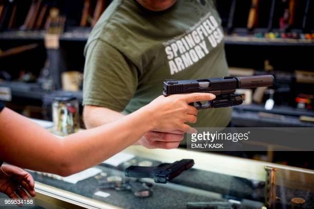Edward Wilks owner of Tradesmen Gun Store and Pawnshop helps Lauren Boebert with a firearm at his store in Rifle Colorado on April 24 2018 Lauren...