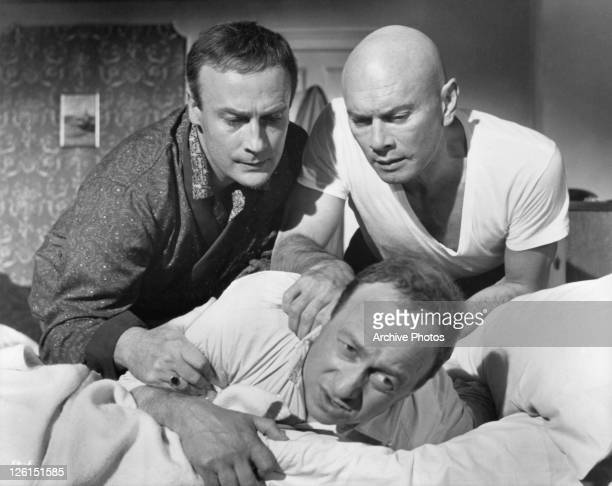 Edward Woodward and Yul Brynner rough up a snooping night clerk at gang's land hotel in a scene from the film 'The File Of The Golden Goose', 1969.