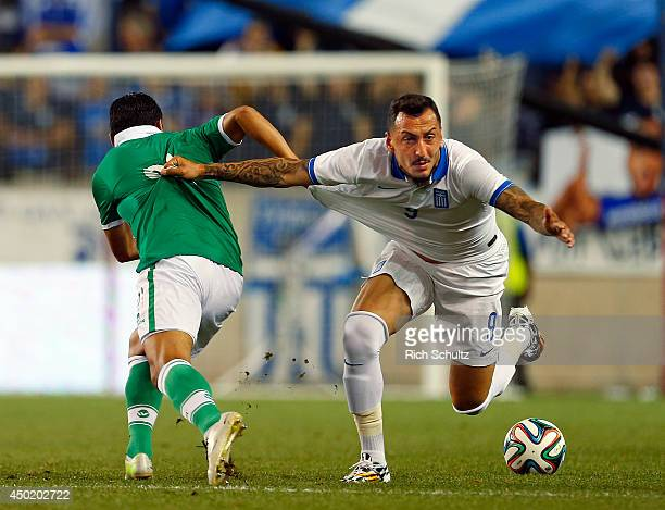 Edward Zenteno of Bolivia battles Kostas Mitroglou of Greece during the second half of an international friendly match at Red Bull Arena on June 6...