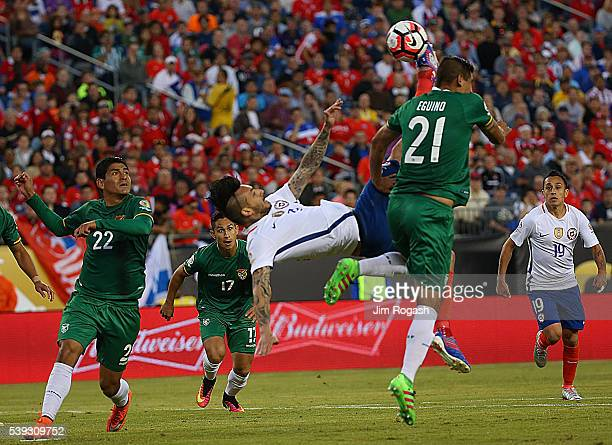 Edward Zenteno of Bolivia defends as Mauricio Pinilla of Chile attempts a bicyclekick shot on net during a 2016 Copa America Centenario Group D match...