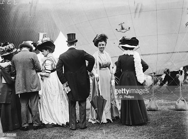 Edwardian ladies and gentlemen attend a hot air ballooning event