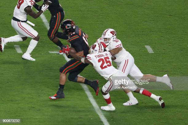 J Edwards and Derrick Tindal of the Wisconsin Badgers tackle Malik Rosier of the Miami Hurricanes as he runs with the ball during the 2017 Capital...