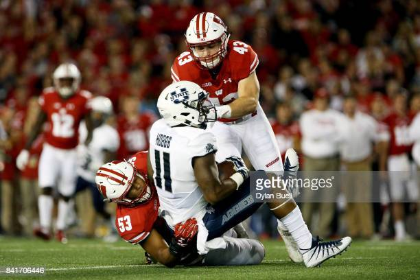 J Edwards and Ryan Connelly of the Wisconsin Badgers combine for a tackle against Damion Hobbs of the Utah State Aggies in the first quarter at Camp...