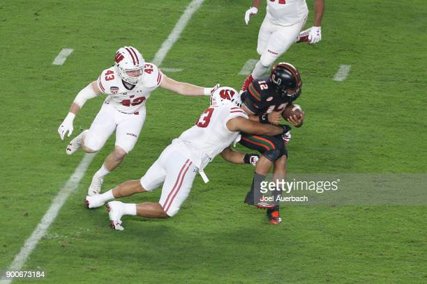 J Edwards of the Wisconsin Badgers tackles Malik Rosier of the Miami Hurricanes as he runs with the ball during first quarter action during the 2017...