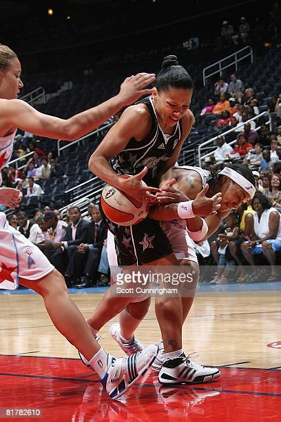 Edwige Lawson of the San Antonio Silver Stars battles for ball control against Betty Lennox and Kristen Mann of the Atlanta Dream during the WNBA...