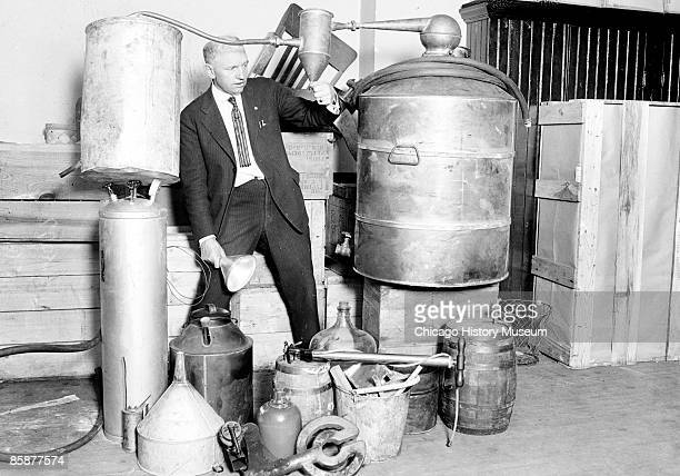 Edwin C Arthur stands in the center of a collection of containers of moonshine taken during a South Side raid in Chicago Illinois 1922