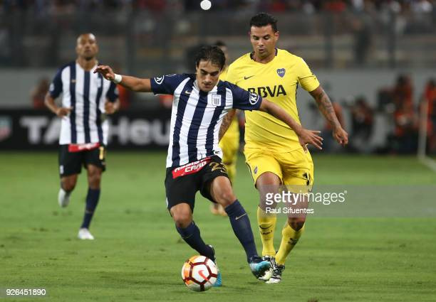 Edwin Cardona Boca Juniors struggles for the ball with Luis Garro of Alianza Lima during a groups stage match between Alianza Lima and Boca Juniors...