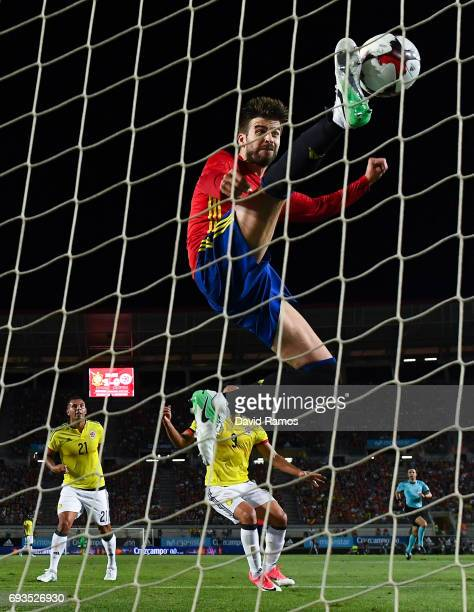 Edwin Cardona of Colombia scores past Gerard Pique of Spain his team's first goal during a friendly match between Spain and Colombia at La Nueva...