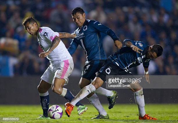 Edwin Cardona of Monterrey fights for the ball with Dionicio Escalante and Mario Osuna of Querétaro during the 15th round match between Queretaro and...