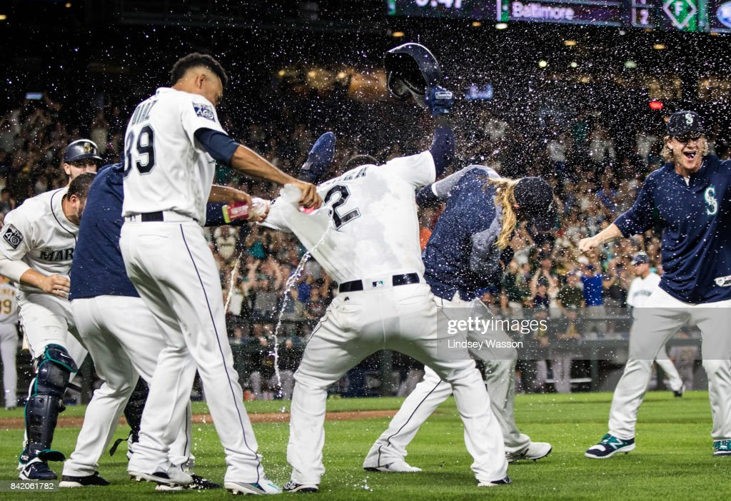 Edwin Diaz #39 of the Seattle Mariners, left throws water on Jean Segura #2, who scored the winning run on a wild pitch by Blake Treinen #39 of the Oakland Athletics in the ninth inning at Safeco Field on September 2, 2017 in Seattle, Washington. The Seattle Mariners beat the Oakland Athletics 7-6.