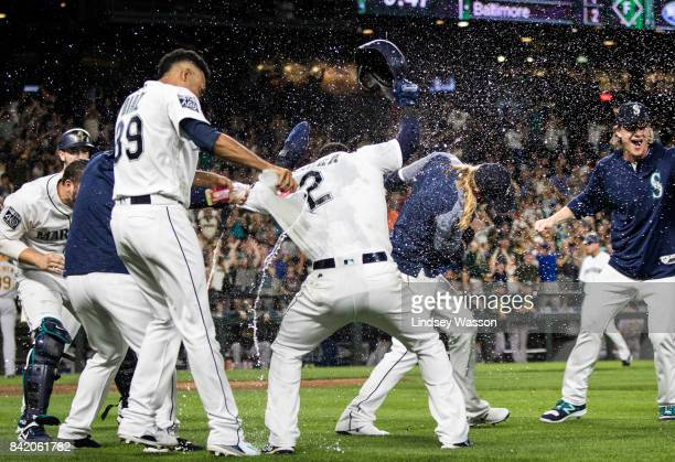 Edwin Diaz of the Seattle Mariners left throws water on Jean Segura who scored the winning run on a wild pitch by Blake Treinen of the Oakland...