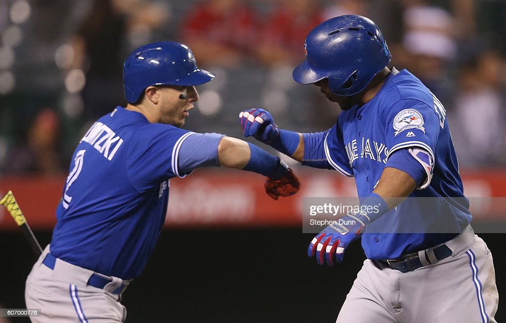 Edwin Encarnacion #10 and Troy Tulowitzki #2 of the Toronto Blue Jays celebrate as Encarnacion returns to the dugout after hitting a two run home run in the ninth inning against the Los Angeles Angels of Anaheim at Angel Stadium of Anaheim on September 16, 2016 in Anaheim, California.