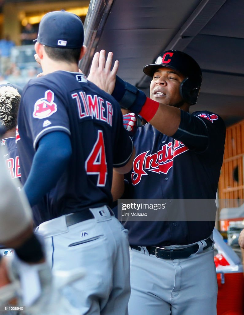 Edwin Encarnacion #10 of the Cleveland Indians celebrates in the dugout with teammate Bradley Zimmer #4 after scoring a run in the first inning against the New York Yankees in the second game of a doubleheader at Yankee Stadium on August 30, 2017 in the Bronx borough of New York City.