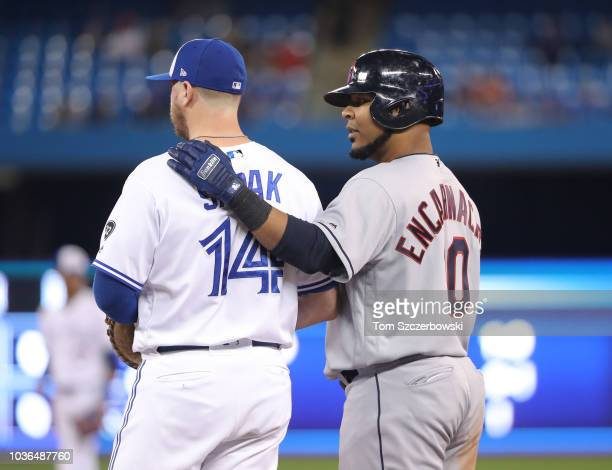 Edwin Encarnacion of the Cleveland Indians embraces former teammate Justin Smoak of the Toronto Blue Jays as they stand at first base after...