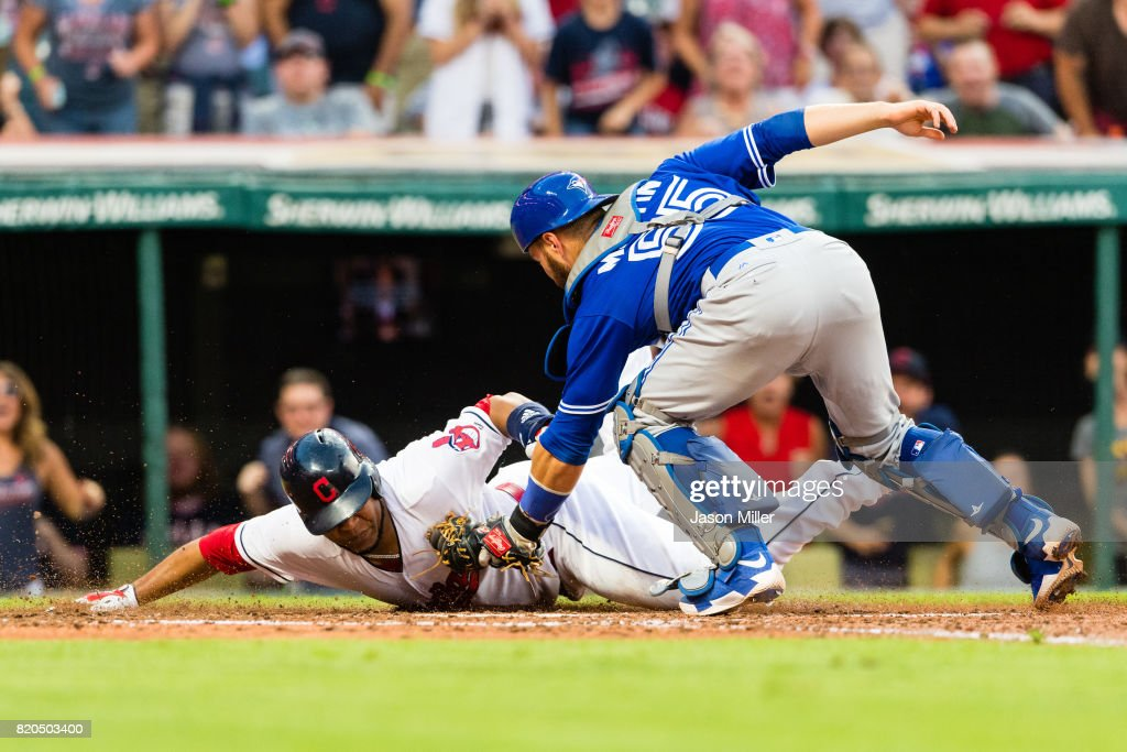 Edwin Encarnacion #10 of the Cleveland Indians is tagged out by catcher Russell Martin #55 of the Toronto Blue Jays to end the fourth inning at Progressive Field on July 21, 2017 in Cleveland, Ohio.
