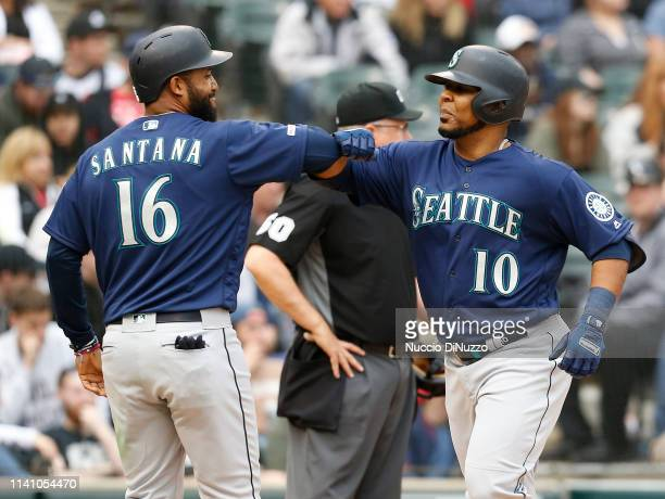 Edwin Encarnacion of the Seattle Mariners bumps elbows with Domingo Santana after hitting a two run home run in the fourth inning against the Chicago...