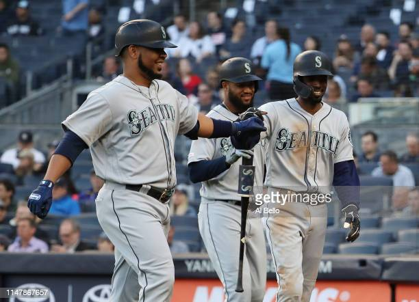 Edwin Encarnacion of the Seattle Mariners celebrates with Dee Gordon after driving him in with a sacrifice fly in the first inning against the New...