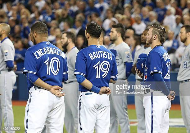 Edwin Encarnacion of the Toronto Blue Jays and Jose Bautista and Josh Donaldson stand for the playing of the anthems before the start of their game...