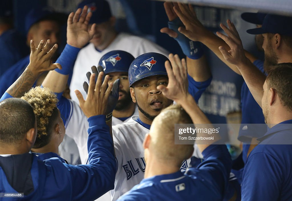 Edwin Encarnacion #10 of the Toronto Blue Jays and Jose Bautista #19 are congratulated by teammates in the dugout after both runners scored on a two-run double by Justin Smoak #13 in the fourth inning during MLB game action against the Boston Red Sox on September 18, 2015 at Rogers Centre in Toronto, Ontario, Canada.