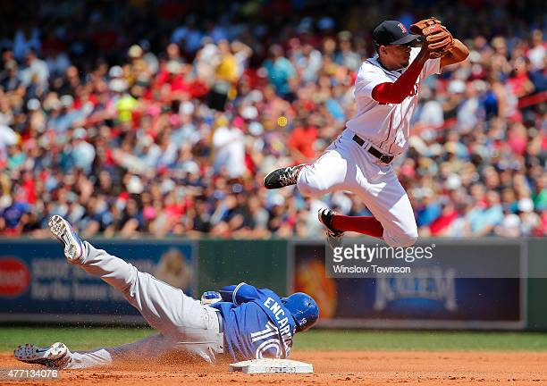 Edwin Encarnacion of the Toronto Blue Jays breaks up a double play as Xander Bogaerts of the Boston Red Sox leaps over him during the fourth inning...