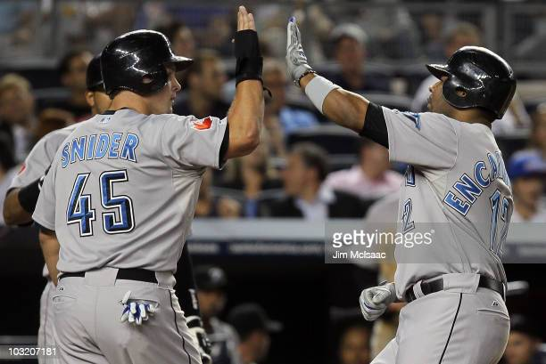 Edwin Encarnacion of the Toronto Blue Jays celebrates his fifth inning two run home run against the New York Yankees with teammate Travis Snider on...