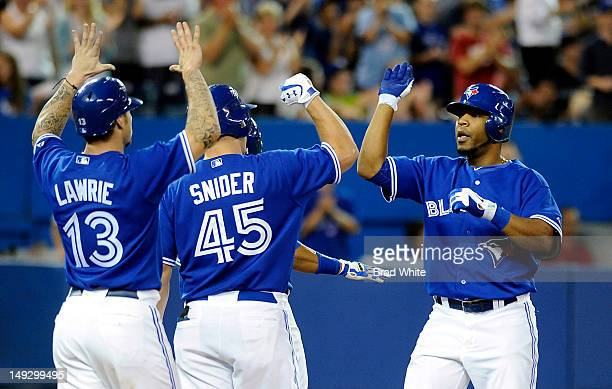 Edwin Encarnacion of the Toronto Blue Jays celebrates his fourth inning home run with teammates Brett Lawrie and Travis Snider during MLB game action...