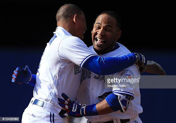 Edwin Encarnacion of the Toronto Blue Jays celebrates with Ezequiel Carrera after hitting a single where Kevin Pillar scored the winning run in the...