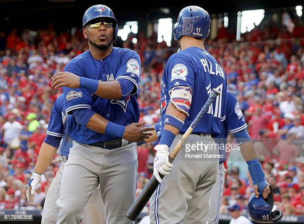 Edwin Encarnacion of the Toronto Blue Jays celebrates with his teammates after scoring a run off of Troy Tulowitzki RBI triple to right field against...