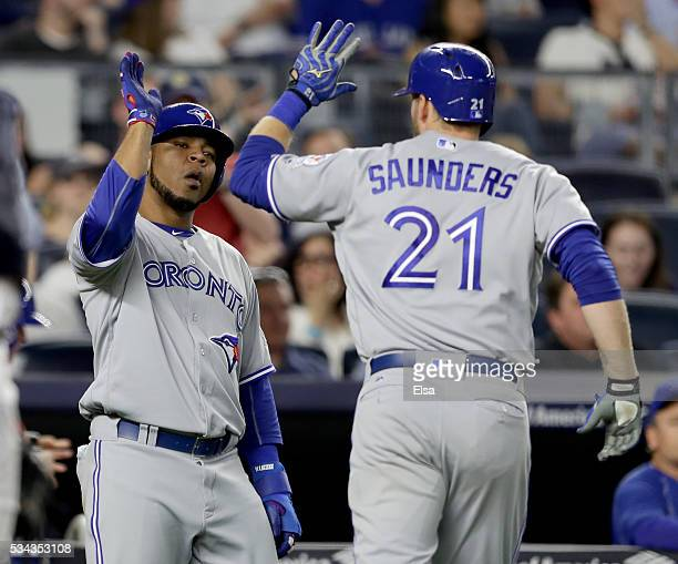 Edwin Encarnacion of the Toronto Blue Jays congratulates teammate Michael Saunders after Saunders drove them both home with a home run in the seventh...
