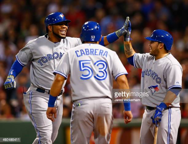 Edwin Encarnacion of the Toronto Blue Jays is congratulated at home plate by teammates Dioner Navarro and Melky Cabrera after hitting his second...