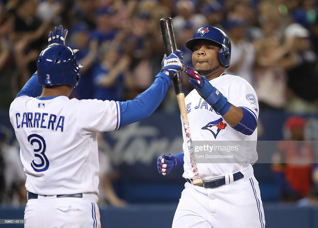 Edwin Encarnacion #10 of the Toronto Blue Jays is congratulated by Ezequiel Carrera #3 as both runners scored on a three-run double by Russell Martin #55 in the sixth inning during MLB game action against the Minnesota Twins on August 26, 2016 at Rogers Centre in Toronto, Ontario, Canada.