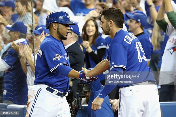 Edwin Encarnacion of the Toronto Blue Jays is congratulated by Chris Colabello of the Toronto Blue Jays after scoring a run in the sixth inning...