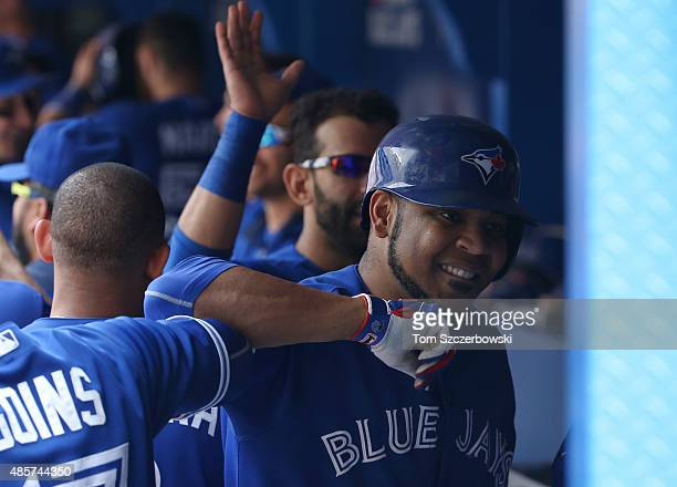 Edwin Encarnacion of the Toronto Blue Jays is congratulated by teammates in the dugout after hitting a grand slam home run in the seventh inning...