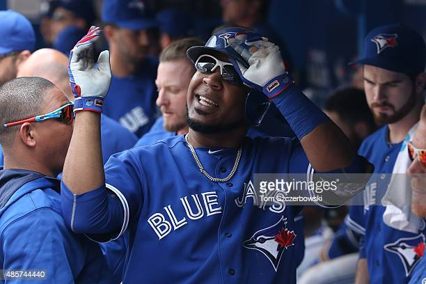 Edwin Encarnacion of the Toronto Blue Jays is congratulated by teammates in the dugout after hitting a tworun home run in the sixth inning during MLB...