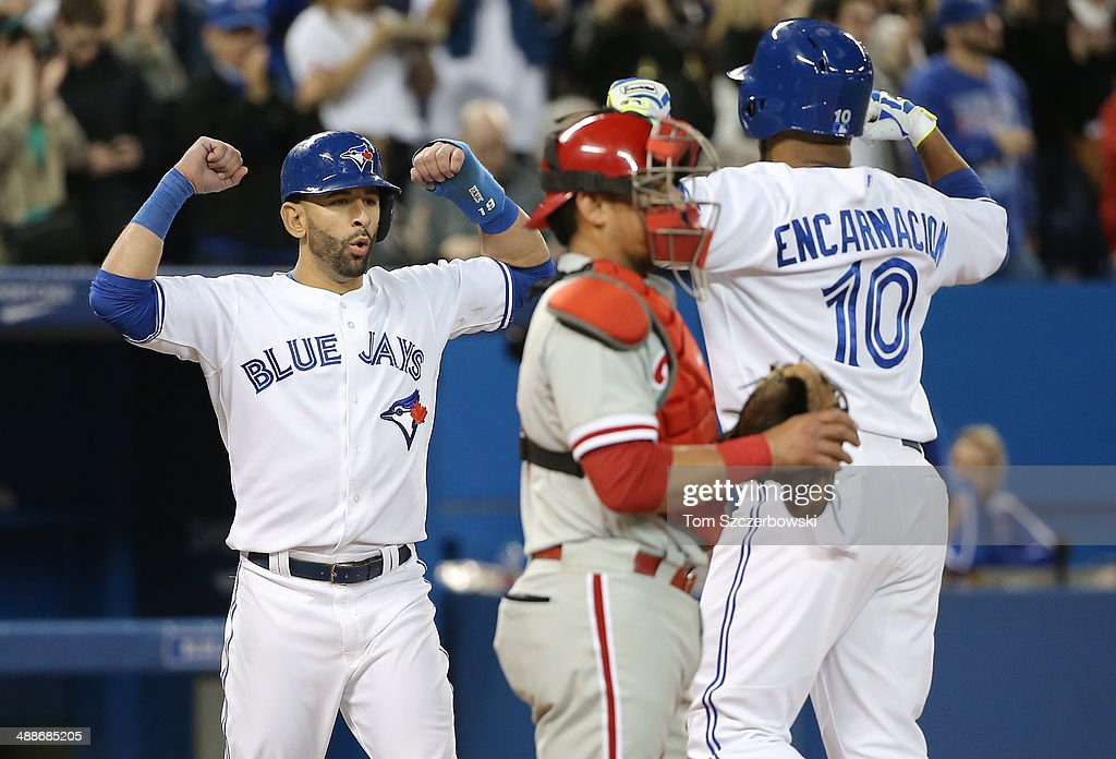 Edwin Encarnacion #10 of the Toronto Blue Jays is congratulated by Jose Bautista #19 after hitting a three-run home run in the seventh inning during MLB game action against the Philadelphia Phillies on May 7, 2014 at Rogers Centre in Toronto, Ontario, Canada.