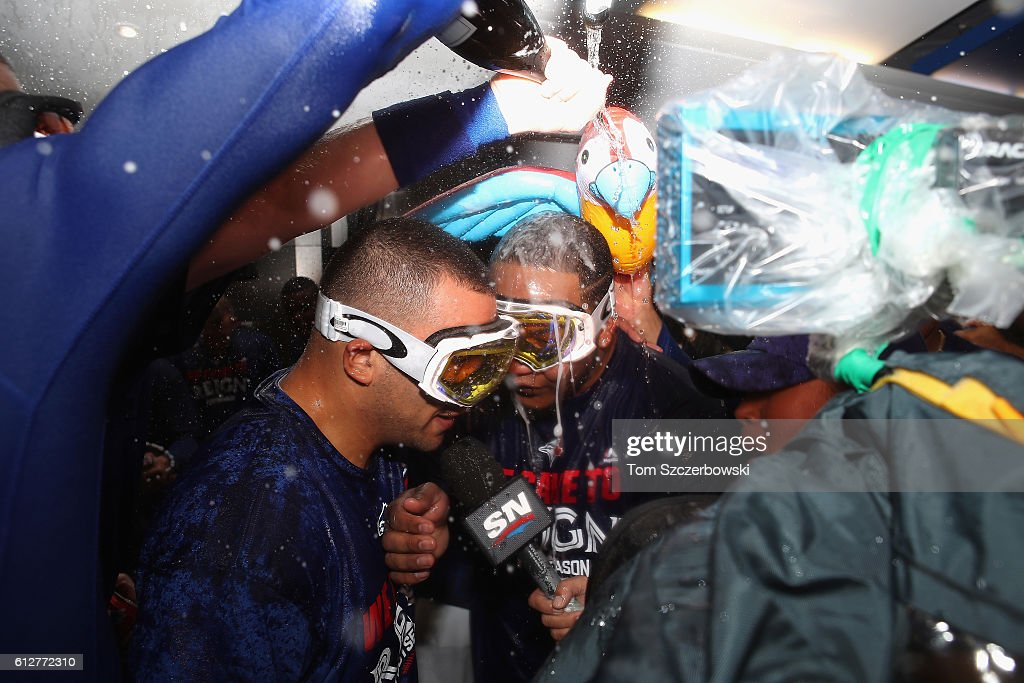Edwin Encarnacion #10 of the Toronto Blue Jays (right-center) is doused with champagne in the clubhouse after hitting a three-run walk-off home run in the eleventh inning to defeat the Baltimore Orioles 5-2 in the American League Wild Card game at Rogers Centre on October 4, 2016 in Toronto, Canada.