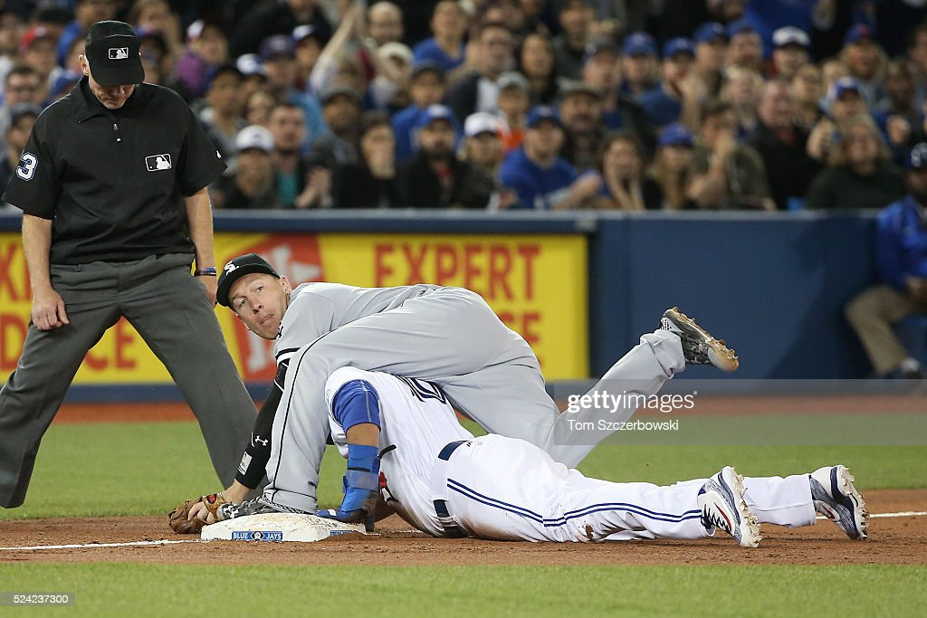 Edwin Encarnacion #10 of the Toronto Blue Jays (bottom) is tagged out at third base by Todd Frazier #21 of the Chicago White Sox as he tries to advance on a single from first base in the third inning on April 25, 2016 at Rogers Centre in Toronto, Ontario, Canada.