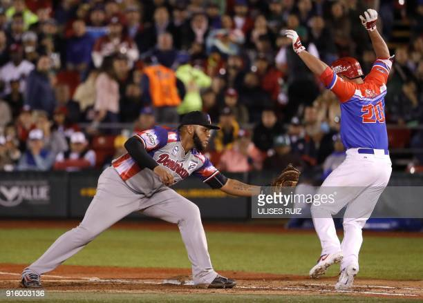 Edwin Espinal of Aguilas Cibaenas of Republica Dominicana takes the ball to put out Johnny Monell of Criollos de Caguas of Puerto Rico during the...
