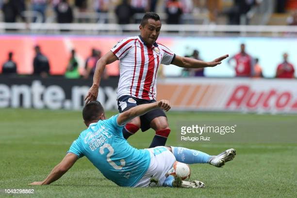 Isaac Brizuela of Chivas fights for the ball with Areli Hernández of Queretaro during the 10th match between Chivas and Queretaro as part of the...