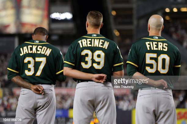 Edwin Jackson Blake Treinen and Mike Fiers of the Oakland Athletics stand during the national anthem prior to the American League Wild Card game...